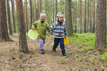 4 year old brother and sister walking with their frisbees through the woods, Sweden