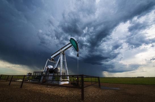 Pump jack, oil well, in field with stormy sky, Canadian praires, Saskatchewan, Canada