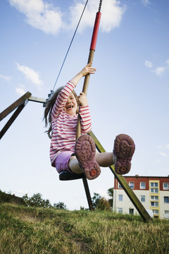 5 year old girl playing with a zip line on a sunny evening, Germany
