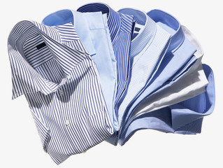 Group of blue and striped men's dress shirts on white background