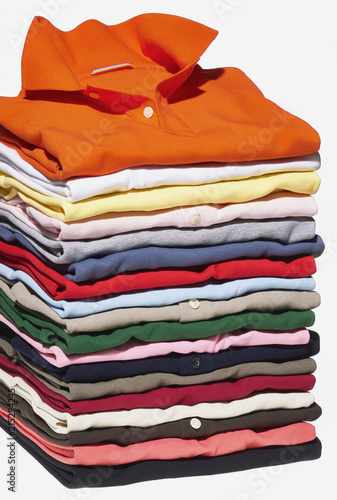 Stack Of Different Coloured Polo Shirts On White Background