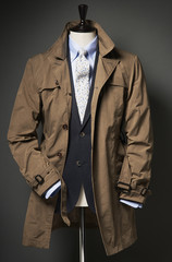 Brown trench coat with suit jacket, shirt and tie on a bust, studio shot
