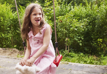 5 year old girl sitting on a swing in the garden, Germany