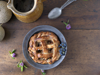 Rustic pie in pewter dish with antique spoon, jug, melon fruit and clover on wooden tabletop