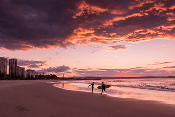 A couple of silhouetted surfers on the beach at Coolangatta, Queensland, Australia, at sunset.