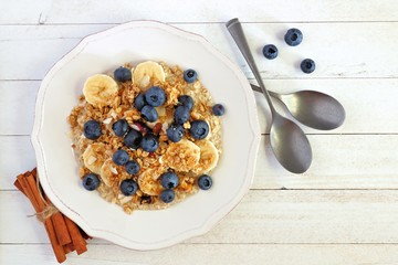 Bowl of breakfast oatmeal topped with blueberries, bananas and granola. Top view over a white wood background.