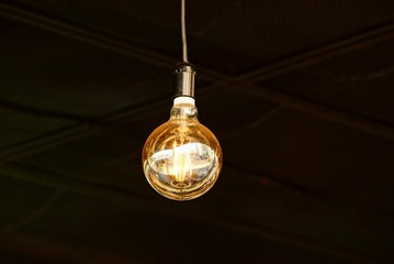 large luminous round light bulb on a cord in a dark room