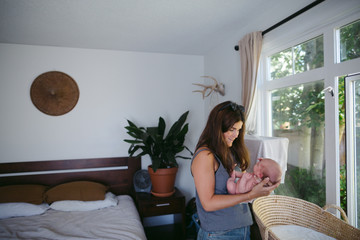 Beautiful young mother holding newborn baby in bedroom