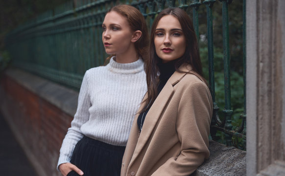 two stylish women posing outdoors