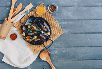 Mussels in white wine sauce over wooden background. Top view, copy space