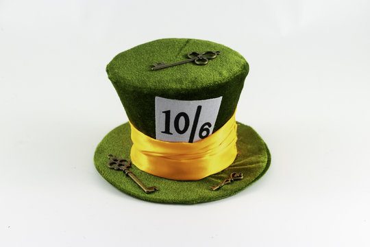 A green wonderland hat with orange band with vintage keys and a queen of hearts card.