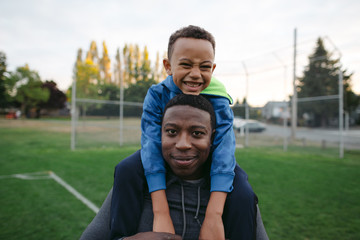 Man and child enjoying shoulder ride together outside in field