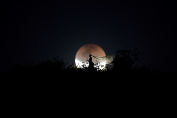 A bride poses for photo during a total lunar eclipse from in Brasilia