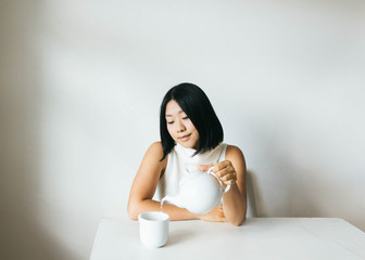 Portrait of young woman pouring tea into cup