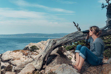 Hiking woman surveying the ocean with binoculars