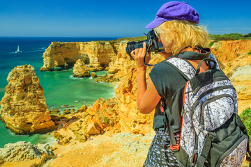 Travel photographer takes shot of iconic natural arches of Praia da Marinha in Algarve. Female tourist takes pictures with professional camera of high cliffs of popular Marinha Beach. Trip in Portugal