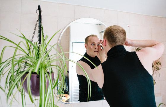 Man applying makeup while reflecting in mirror