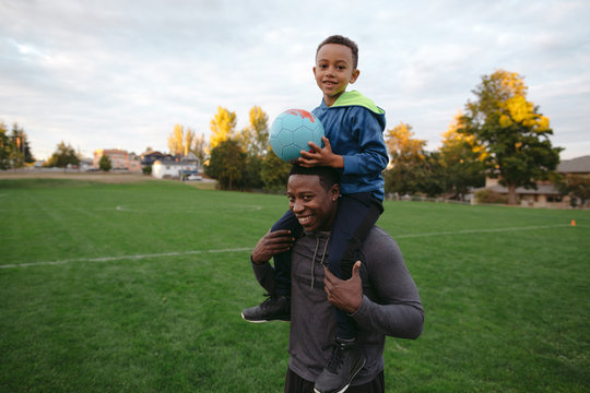 Man giving child shoulder ride with soccer ball at park