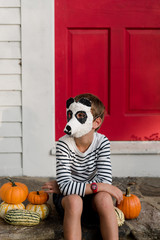 little boy in front of red door with panda bear mask in the fall