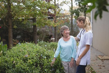 Physiotherapist and senior woman talking at the backyard