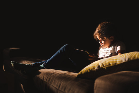 Young girl watching a digital tablet in a dark room