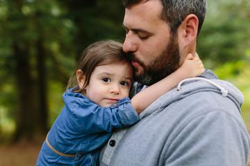 Adorable Little Girl Cuddles on Dad's Shoulder