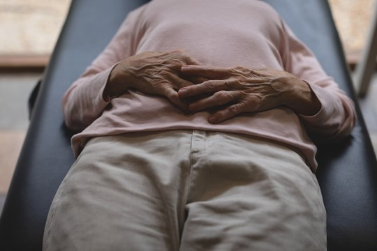 Senior woman lying on bed with hand on stomach