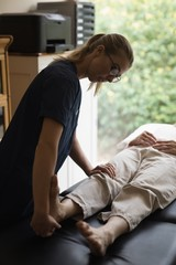 Physiotherapist giving a leg massage to senior woman