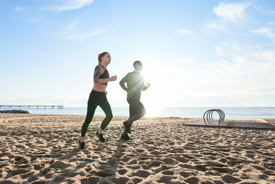 Couple running on the beach in morning.