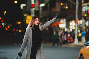 Young woman hailing a cab at night