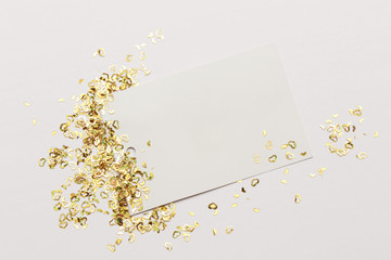 Many golden hearts confetti and blank paper isolated on the white background. Festive holiday background. Celebration concept.