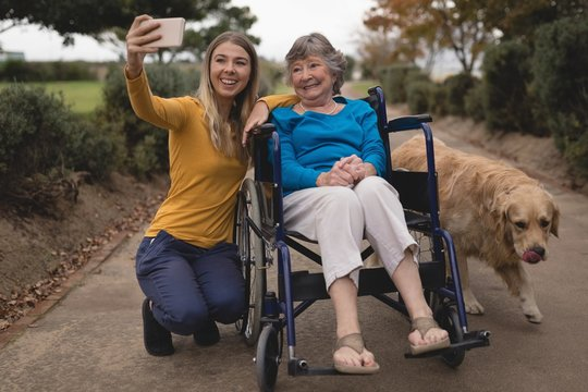Granddaughter and grandmother taking a selfie on mobile phone