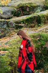 Young woman covered with red wool plaid