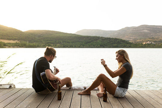Beautiful young couple playing the guitar and taking photos near