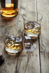 Two glasses of single malt Scottish whisky with ice on a wooden table.