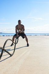 Muscular man training with ropes