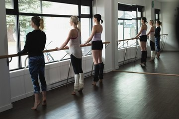 Group of women stretching holding the barre