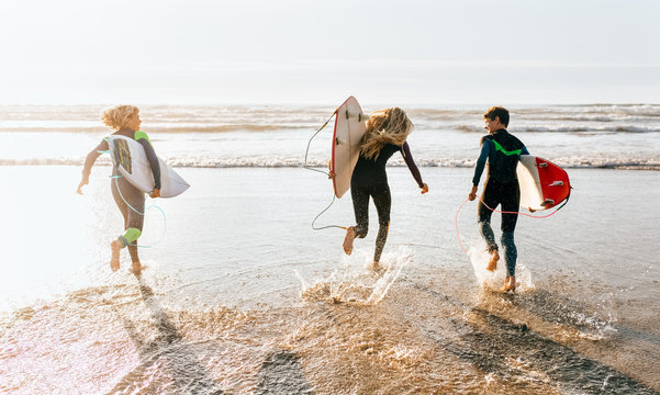Three teenage friends heading out to sea for surfing