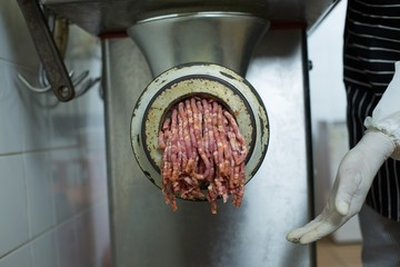 Butcher using machine to minced meat