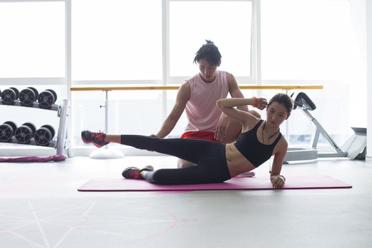 Young asian woman work out in the gym with her coach