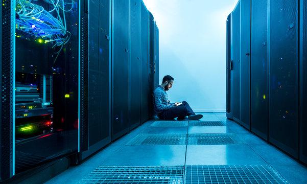 Technician entering data on a digital tablet in a server room