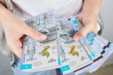 Tenge. A girl in a white t-shirt holding a lot of Kazakh bills close-up..