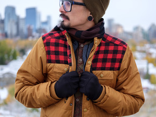 A man holds onto his trendy autumn jacket.