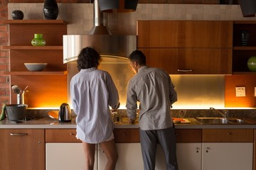 Couple preparing food together in kitchen at home