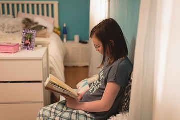 Girl reading a book in bedroom