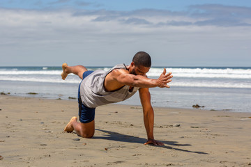 Athletic man at the beach doing yoga on the sand in Balancing Table Pose