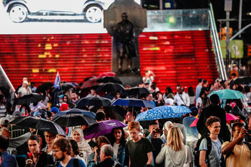 People walk at Times Square during a rainy day in New York City