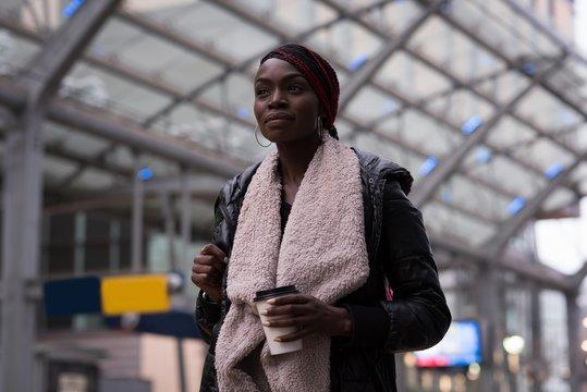 Woman having coffee at railway station