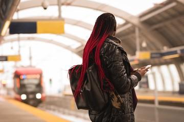 Woman using mobile phone at railway platform