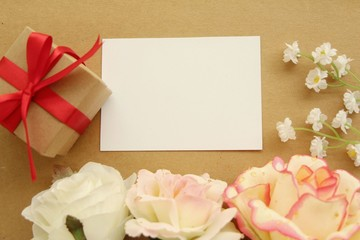 White blank greeting card with gift box red ribbon and flower,flat lay.